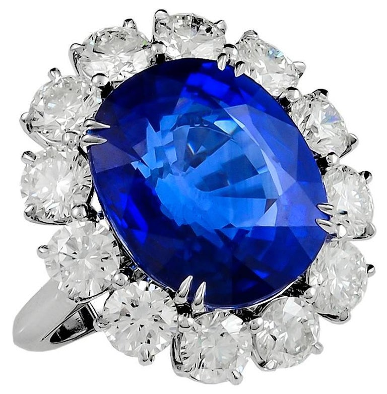 Cushion-cut heated sapphire, surrounded by 12 round brilliant-cut diamonds weighing approx. 4.50 cts. ring. Sapphire weighing 16.807 cts. accompanied by SSEF certificate.  ring size 6.5