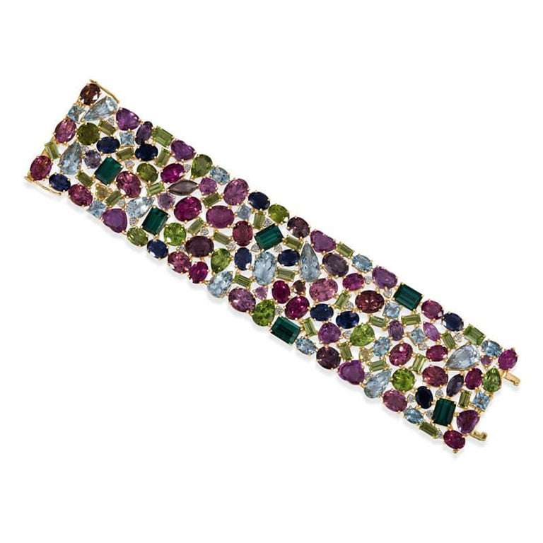 Exceptionally designed wide bracelet in 18KT yellow gold featuring a mixed assortment of colored tourmaline gemstones (in pale and dark green, varying colors of pink, yellow, light and deep blue) in a variety of shapes including heart, pear, oval,