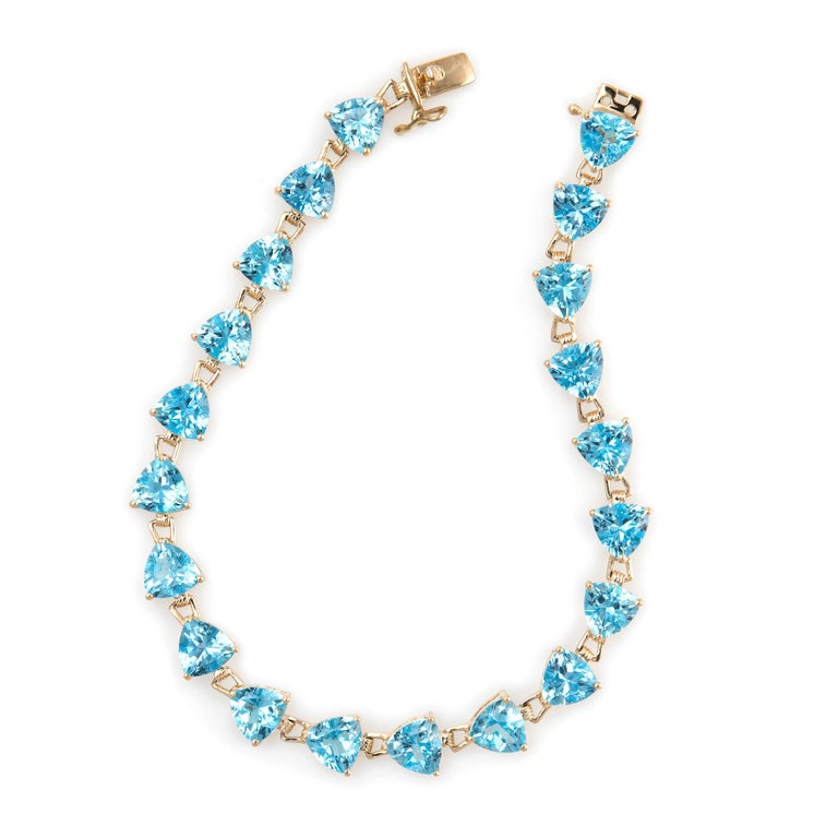 Stylish and finely detailed estate blue topaz bracelet, crafted in 14 karat yellow gold.   20 trillion cut blue topaz measure 6mm (each) and total an estimated 16 carats. The blue topaz is in excellent condition and free of cracks or chips.   The
