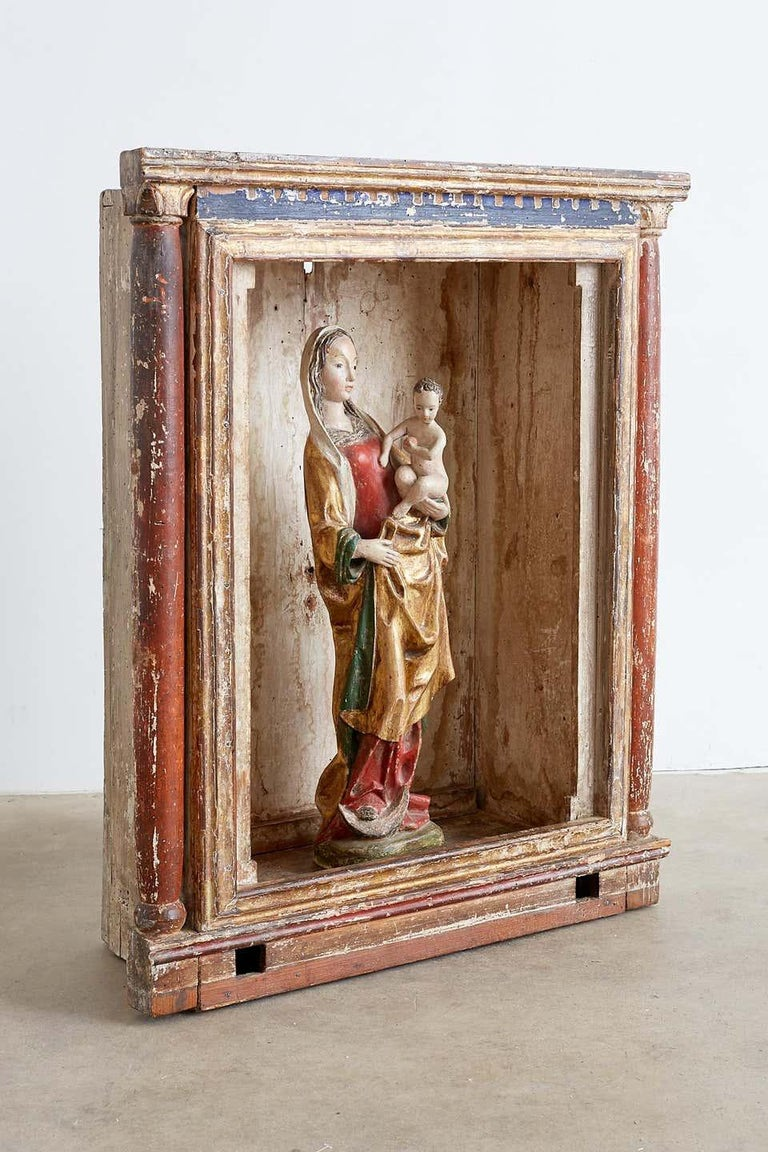 Extraordinary polychromed 16th century Madonna and child from a French monastery. Solid carved wooden Santos statue featuring gilded flowing robe and polychrome finish. The Madonna or Virgin Mary has an exceptionally beautiful face and rich patina.