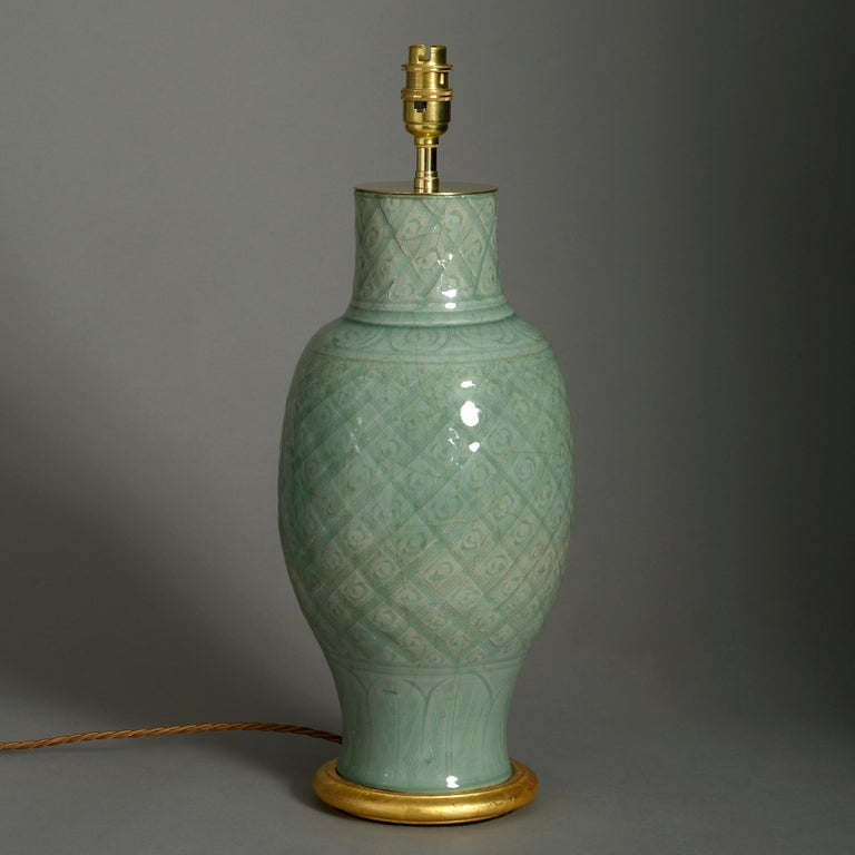 A mid-16th century celadon porcelain vase, the body with inscribed crosshatching and foliate decoration. Now mounted on a turned giltwood base and wired as a lamp. Neck slightly reduced.  Ming Period, circa 1550  Height dimensions refer to vase