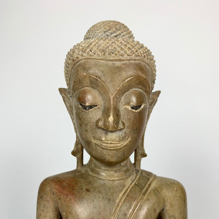 16th or 17th century Northern Thai carved stone Buddha. Phayoa stone and style resting on a fitted stand. Buddha dimensions: 8 1/2 x 6 x 3 inches; overall dimensions: 10 x 6 1/2 x 4 inches. Provenance: From the Private collection of Konrad and