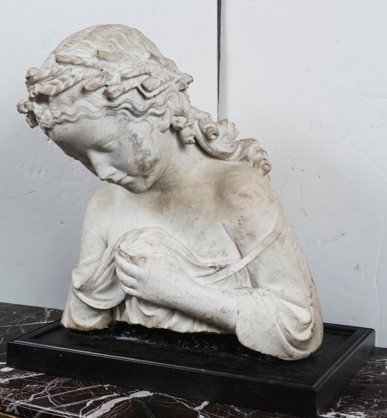 This bust is a fragment of a full figure marble statue of a woman. A modern base has been made for it. She wears classical garb. Her left hand seems to be holding up the garment over her breast. Her right arm is missing. Her head bent forward which