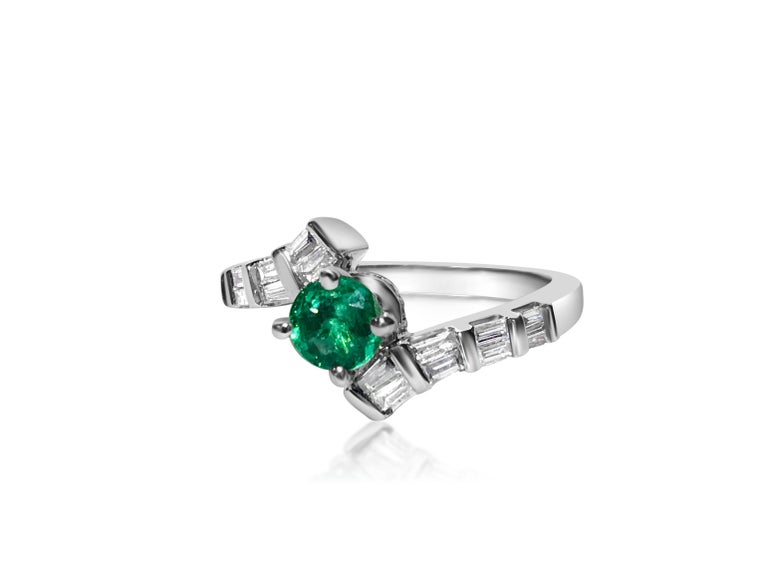 Metal: 14K white gold. 1.00 carat diamonds total. VS clarity and G color. Baguette cut diamonds.  0.70 carat Colombian Emerald, round cut. All stones are 100% natural earth mined.  TCW of all stones: 1.70 carat.  Art Deco style emerald diamond