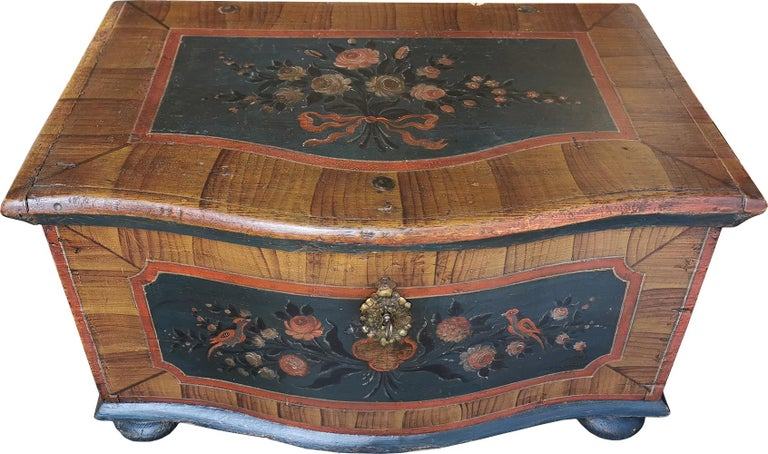 Rare shaped painted chest  Rare painted Tyrolean (North Italy) chest. The rarity is given by the shaped crossbow form. The chest is painted with faux wood decoration, and numerous panels depicting bunches of flowers and little birds. Original