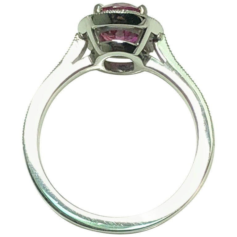A Oval cut Ruby weighing 1.71 carats set in platinum. The ruby is set in a cluster of single cut diamonds with single cut diamond shoulders  The ring size is US 5 1/2.