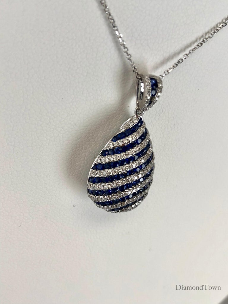 This gorgeous teardrop pendant features 1.74 carats vivid blue Sapphire, with 0.70 carats round white diamonds, arranged in gently curving stripes. Additional stones decorate the bail.  Center: 1.74 carats blue Sapphires Total diamond weight 0.70