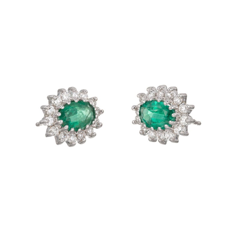Green oval emeralds with a halo of round full cut diamonds, in 18k white gold.   28 round full cut diamonds, approx. total weight .56cts, G, VS 2 oval top fine bright gem green oval Emeralds 7 x 5mm, approx. total weight 1.75cts 18k White