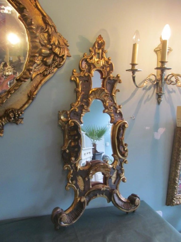 Antique Baroque table mirror from circa 1750. Made of basswood this single piece from a church in Germany convinces with its stunning carving works and the original gilding. The gilding has age related abrasions, but is in great original condition.