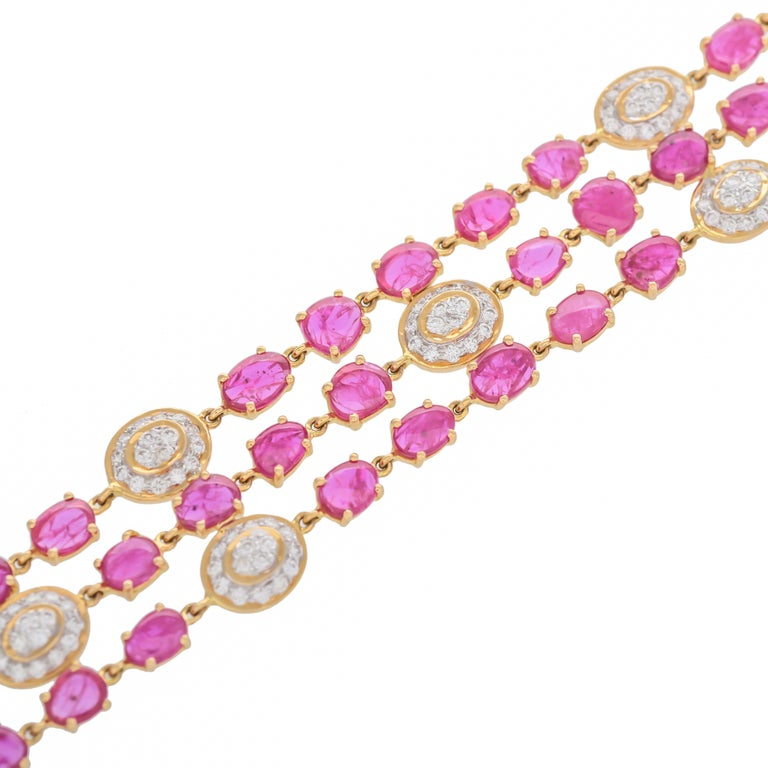 This elegant bracelet comprises of three rows of oval-shaped ruby flats well-matched in lustre, tone and saturation with a total ruby weight of approximately 17.77 carats, connected to a diamond set oval framed in a flexible mesh setting to a