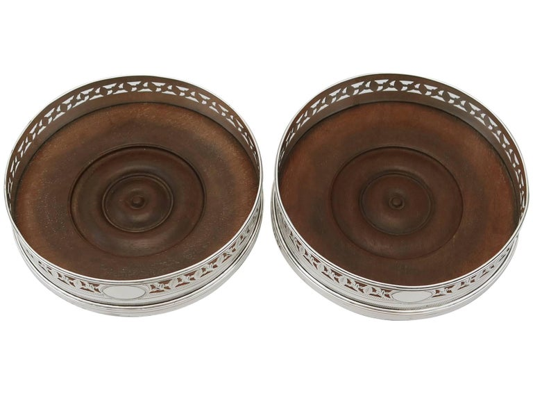 An exceptional, fine and impressive pair of antique Georgian English sterling silver coasters; part of our wine and drinks related silverware collection