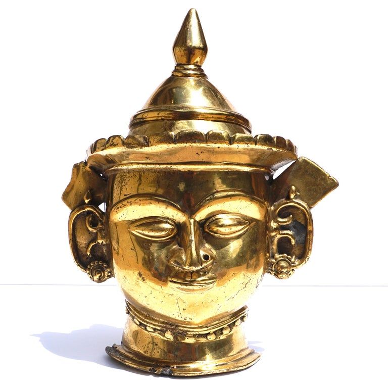 A Indian Mukhalingam Mukha face Lingum mask. A decorative gilt bronze Shiva facial representation of a Hindu God for phalic Lingums. A rare ritual artistic artifact.   Dimensions: 12 x 10 x 3.5 inches  Condition: Very good with wear and restorations