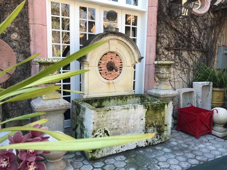 This exquisite water fountain is created of beautifully carved old elements. A rare late 17th-early 18th century stone window Oeil-de-boeuf from an old Chateau in Dordogne. It's crowned with a handsome stone sphere finial. The mythical dolphin