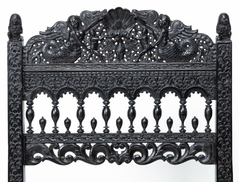 An Indian ebony low chair formerly owned by the Duke of Westminster  Coromandel coast, possibly Madras, 1680-1700  Overall densely carved with an array of mermaids, birds, fish, mythological figures and floral and vine motifs, the back-rails are