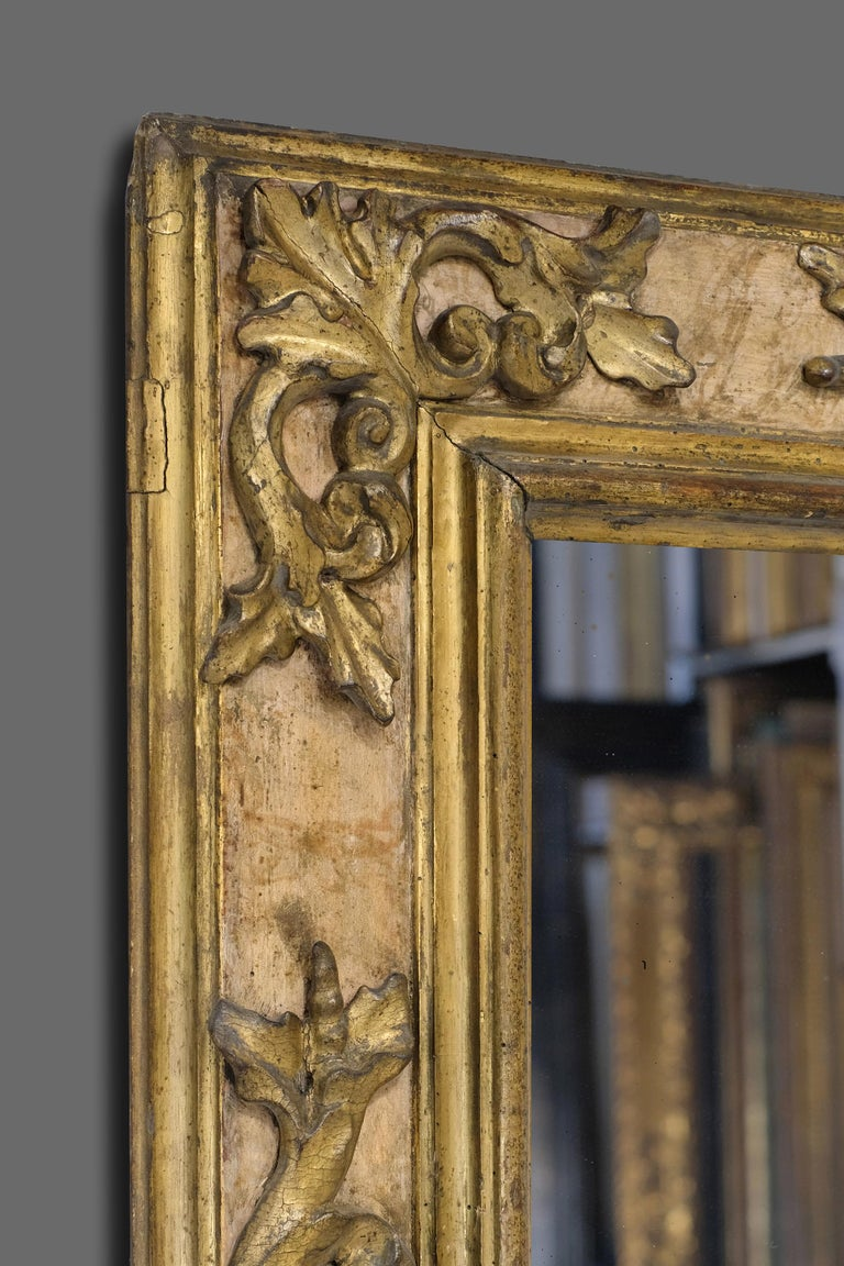 This is a beautifully hand carved, 17th century Italian (Tuscan) Baroque cassetta frame. It has a bolection - architrave profile with carved applied corner-&-center openwork foliate C-scrolled cartouches. The frame retains it's original matte and