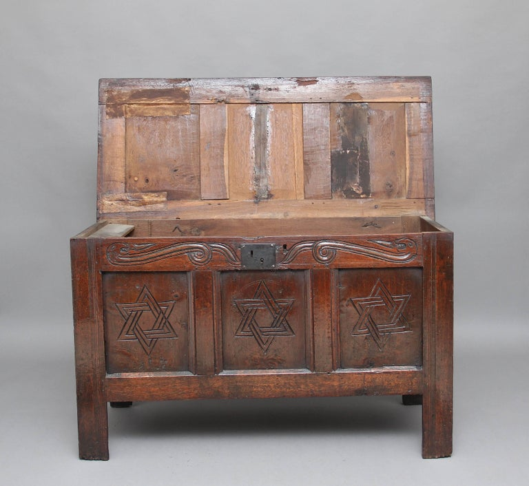 17th century oak coffer with the hinged three panelled top above a three panelled front with carved decoration, a wonderfully carved top rail above the three panelled front, standing on square legs, circa 1680.