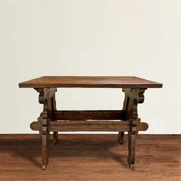 A fantastic and remarkable 17th century Dutch double-sided oak trestle table with beautifully carved ends with curved legs, and stylized floral carved spandrels. The top is well-worn with a patina that only four hundred years of use can bestow.