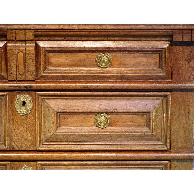 An English antique oak chest of drawers. Charles II period (1630-1685).  The drawer fronts with walnut inserts. The substantial moulded top has cleated ends. Containing four full-length pull-out drawers, the top drawer fitted with divisions, and