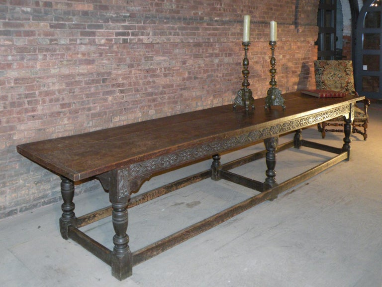 An extraordinary 14 foot long English (Yorkshire) refectory table, of mid-17th century Charles II period, with a substantial two-board elm top above a frieze with carved decoration on one long side, supported by six baluster-turned legs joined by