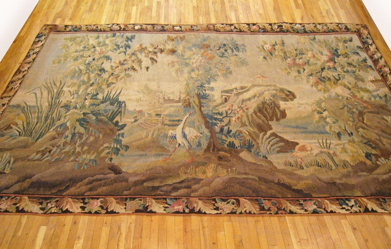 A Flemish chinoiserie landscape tapestry from the 17th century, picturing an idyllic scene with a stately white heron amidst the trees of the verdant foreground, an elegant pagoda overlooking the lake in the middle distance, and a castle amongst the