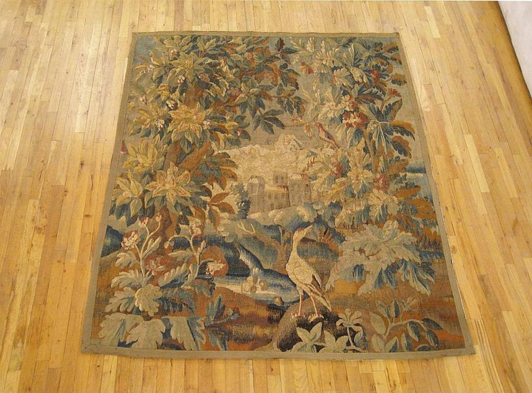 A Flemish verdure landscape tapestry from the 17th century, envisioning an idyllic scene with a heron on a grassy bank between various flora and trees in the foreground, with a pond in the middle distance and a stately manor amidst the rolling hills
