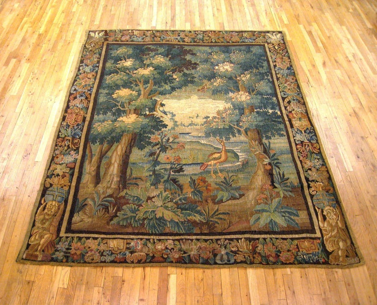 """A Flemish verdure landscape tapestry from the 17th century, depicting a crane in a park between large trees and exotic foliage, within fruiting and flowering borders incorporating allegorical figures and birds. Wool with silk inlay. Measures: 9'5"""" H"""