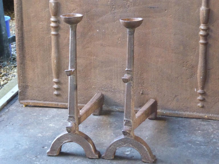 17th century French Gothic Andirons made of cast iron. The andirons have spit hooks to grill food and cups to keep drinks warm. This type of andirons is also called cup dogs. The patina of the andirons is brown. Upon request it can be made