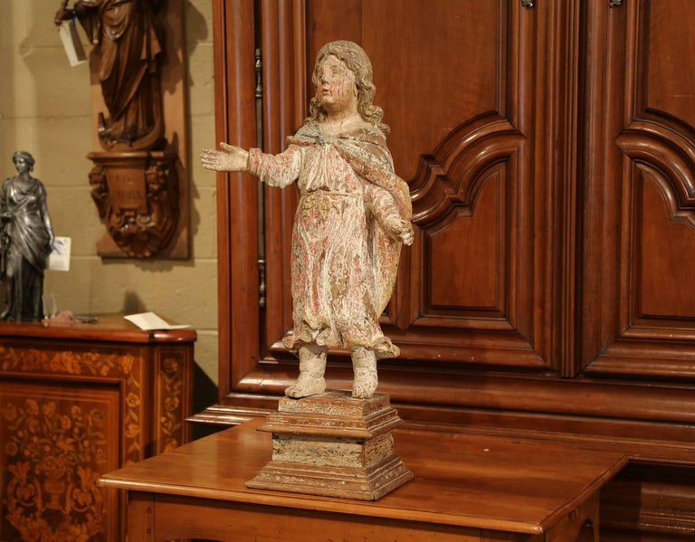 This exquisite, antique figure was carved in Southern France, circa 1650. Standing on a square walnut base, the detailed statue features a young child with long hair with a right hand up. The young adult is wearing a traditional tunic with a