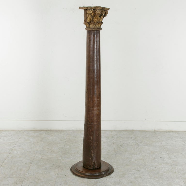 Hand-carved from top to bottom from a single piece of walnut, this 17th century pillar or column features a Corinthian capital with vestiges of its original gilding. Above the beveled circular platform around the base of the pedestal are worn