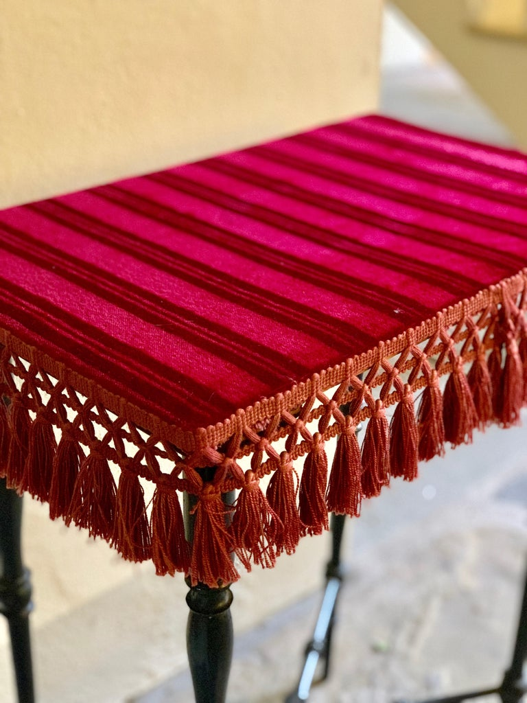 Delicate, playful occasional table of 17th century French origin. The base is ebonized fruitwood, turned and shaped, crossing in a Classic X-joint at the bottom.  The top is finished with a striped crimson velvet and cherry red tassels around the