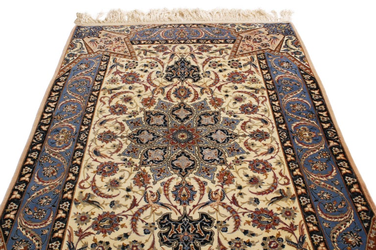 Hand knotted in high-quality wool and naturally luminous silk originating from Persia in the 1970s, this Isfahan Persian rug was inspired from a remarkable 17th century field design with unique, dimensional border permeating the field in the form of