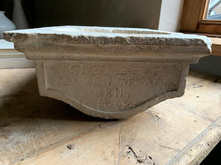 A small 17th century French basin, so called 'benitier'. These were originally used in churches and chapells to contain holy water. Now they make a perfect basin for powder rooms. This one is dated 1669 and inscribed with a Latin text.