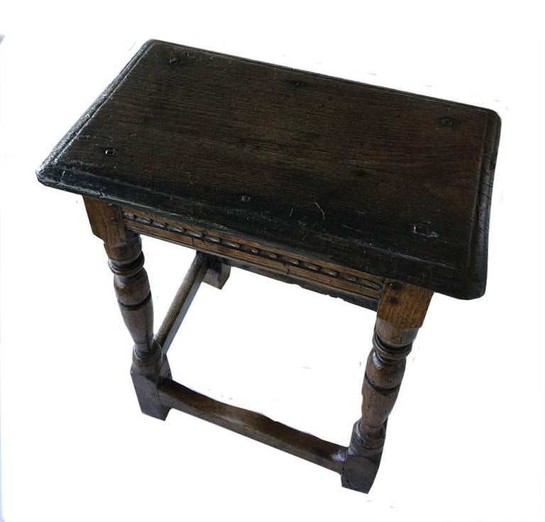 17th century oak joint stool  An exceptionally high standing 17th century oak joint stool with a moulded edge top. Channel moulded rails, cylinder and vase turned legs.  Excellent colour and patin.   Measures: 45 cm wide 53 cm high 27 cm