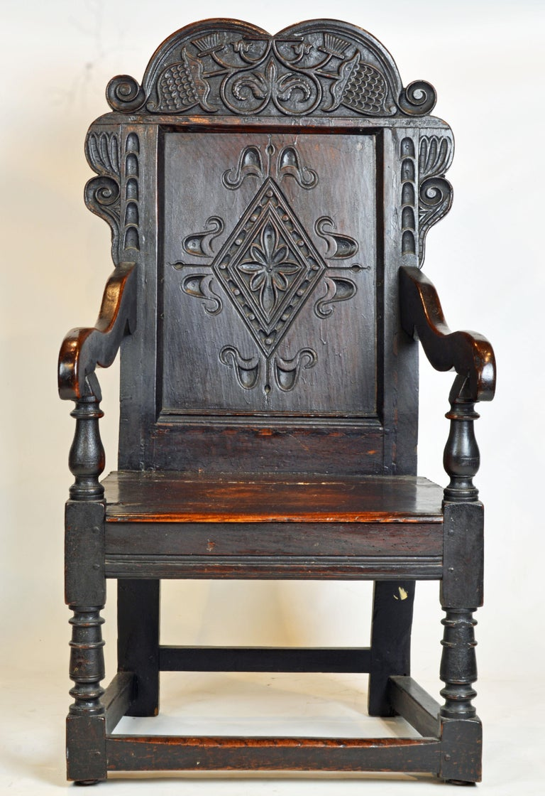 The style of this Elizabethan joined oak chair made in the mid-1600s is a descendant of the Tudor era Wainscot chairs only now without the boxed storage area beneath the seat. The front arm supports are baluster turned and protrude through the seat