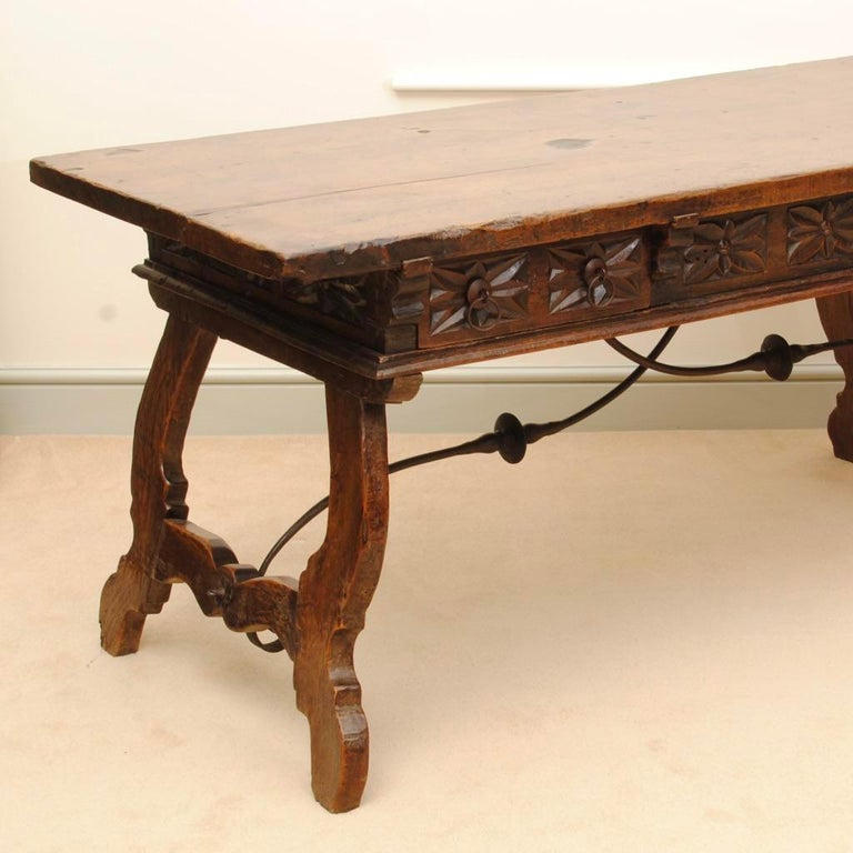 A fine large Spanish walnut table with three drawers to the frieze all with fine carved decoration. The table can be free standing as it has a carved frieze to the rear. With original metalwork stretchers to support the legs.