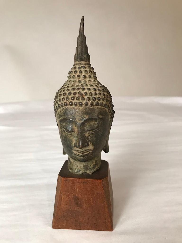 A Thai, Ayutthaya style, bronze head of Buddha Shakyamuni, late 16th or early 17th century. With a serene expression on his face, downcast eyes, arched eyebrows, smiling lips, with curled headdress and ushnisha topped by a flame.  Measures: 6.75