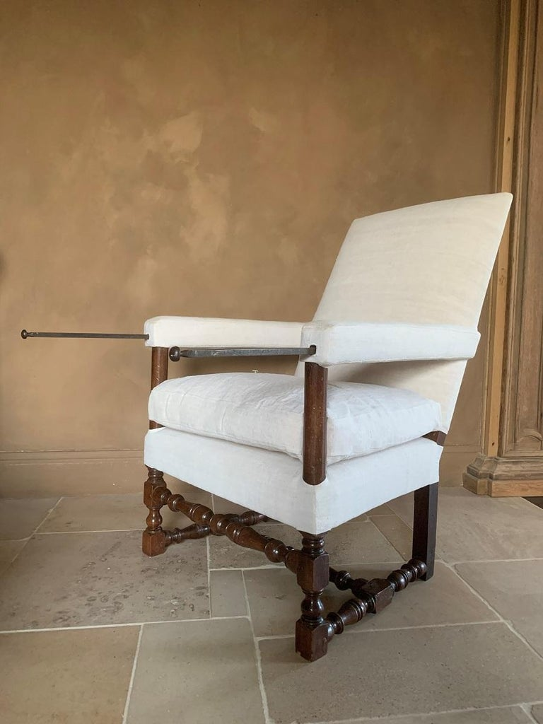 A 17th century French walnut armchair from the Dordogne region. The typical baluster shaped legs under a high back with upholstered armrest concealing tray supports. Armchairs as these were reserved for the upper classes. The larger part of people