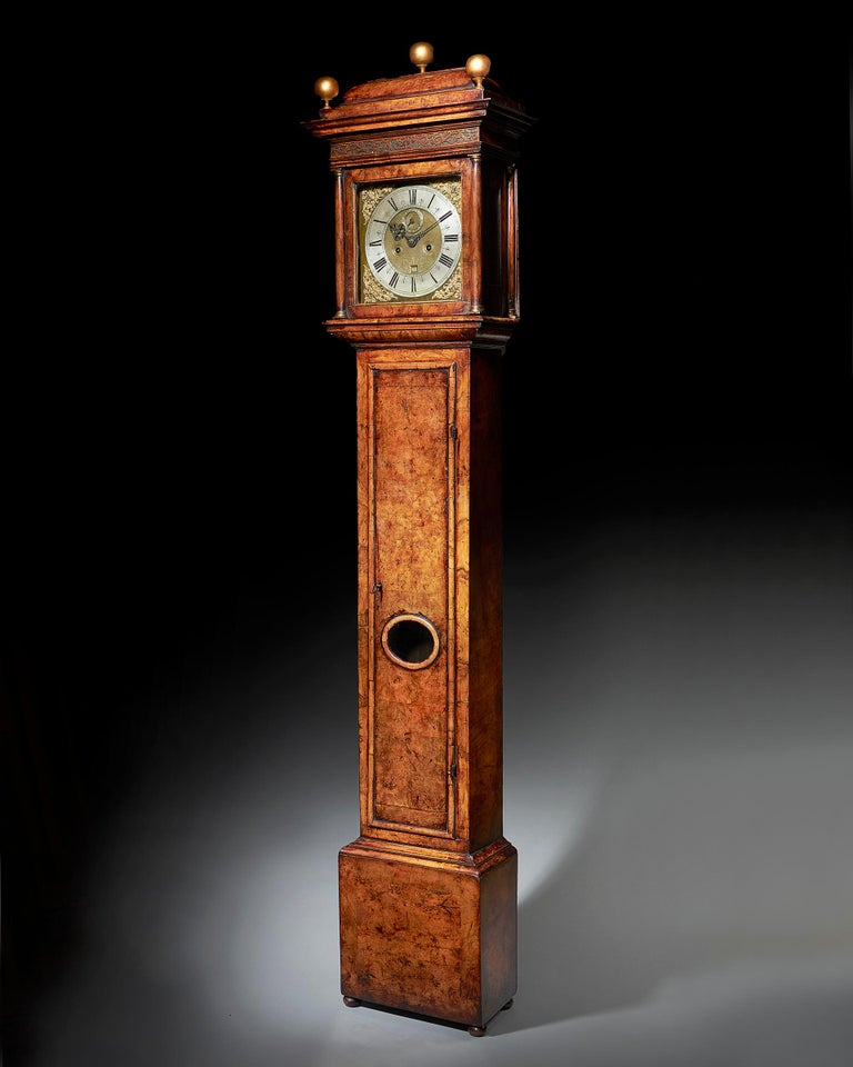 The attractive burr walnut-veneered oak case is of classic design for the period and has a warm patina. The formerly rising hood has a shallow caddy, lovely blind fretwork in the frieze, is flanked by plain brass-capped columns and has glazed