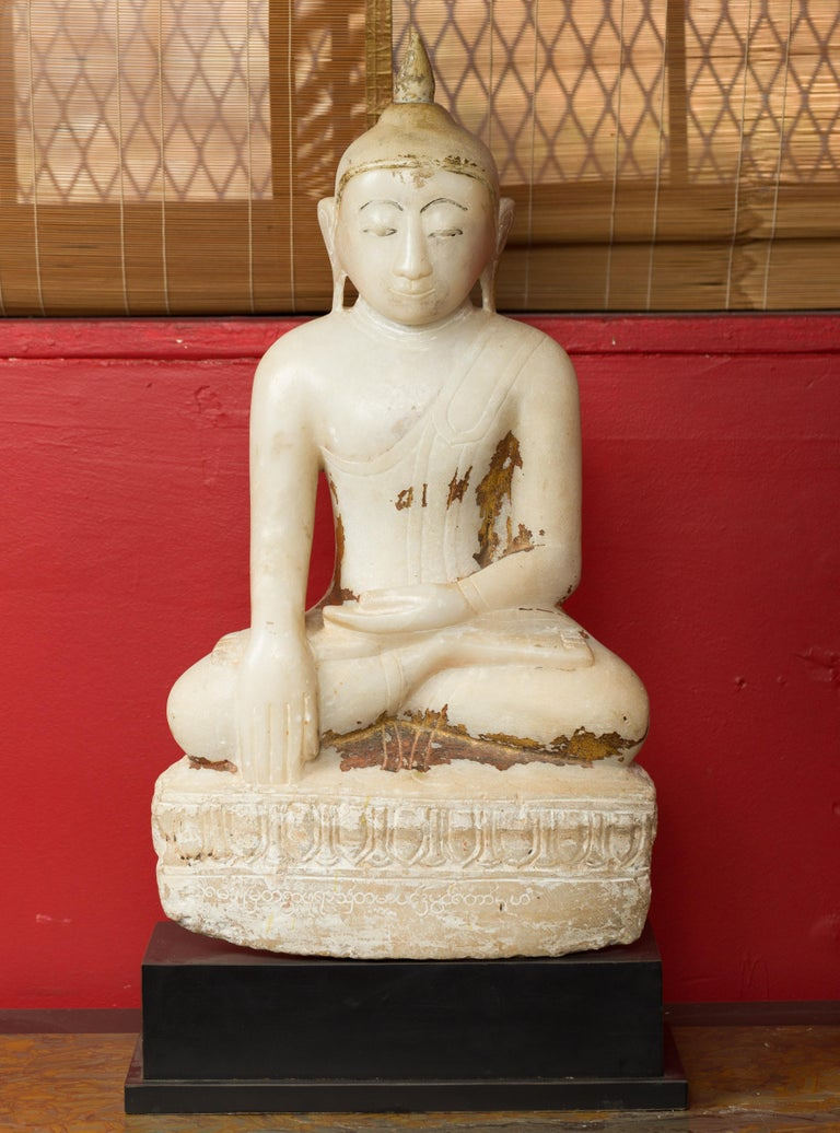 An alabaster 17th or 18th century Burmese Shan style seated Buddha with traces of polychromy. This 17th-18th century seated Buddha was carved in the Shan style from alabaster in Myanmar, a Burmese region. The Buddha is seated in the attitude of