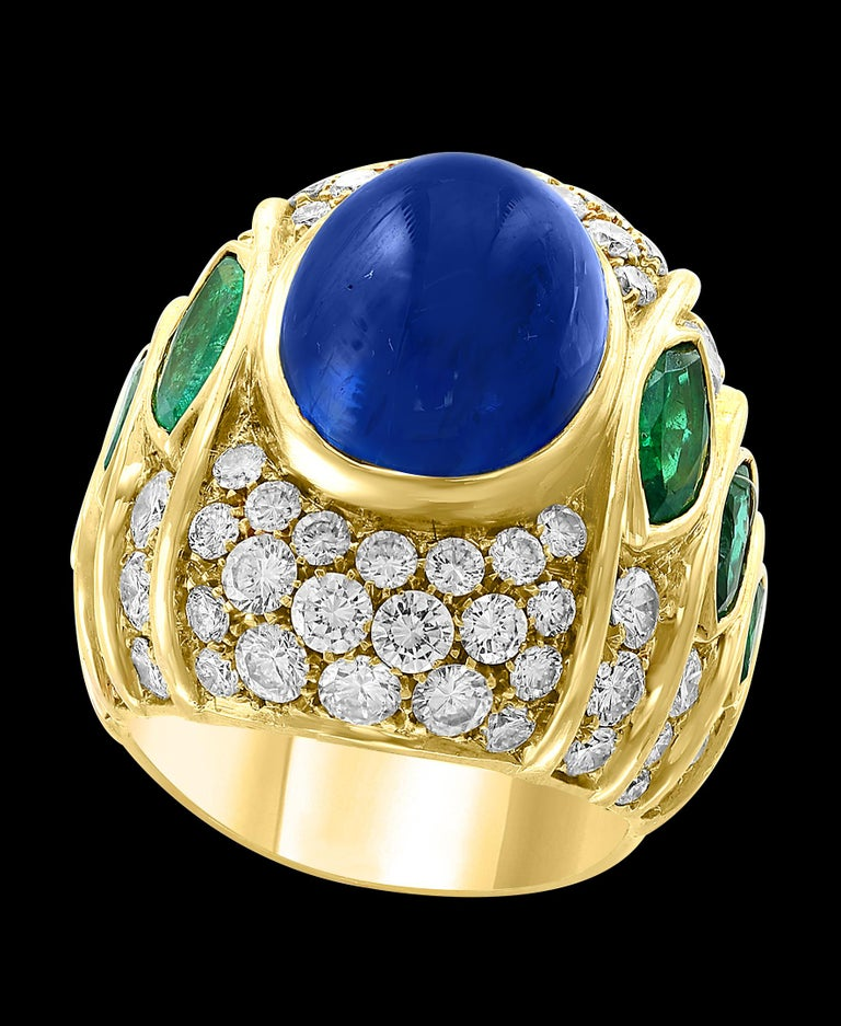 18 Carat Blue Sapphire Cabochon natural  Diamonds 4.5 ct of  brilliant  Round cut diamonds. 3 Marquise shape Emeralds on each side. 18 K yellow gold 26 Grams Unisex ring  All our jewelry comes with a certificate appraisal and money back guaranteed.
