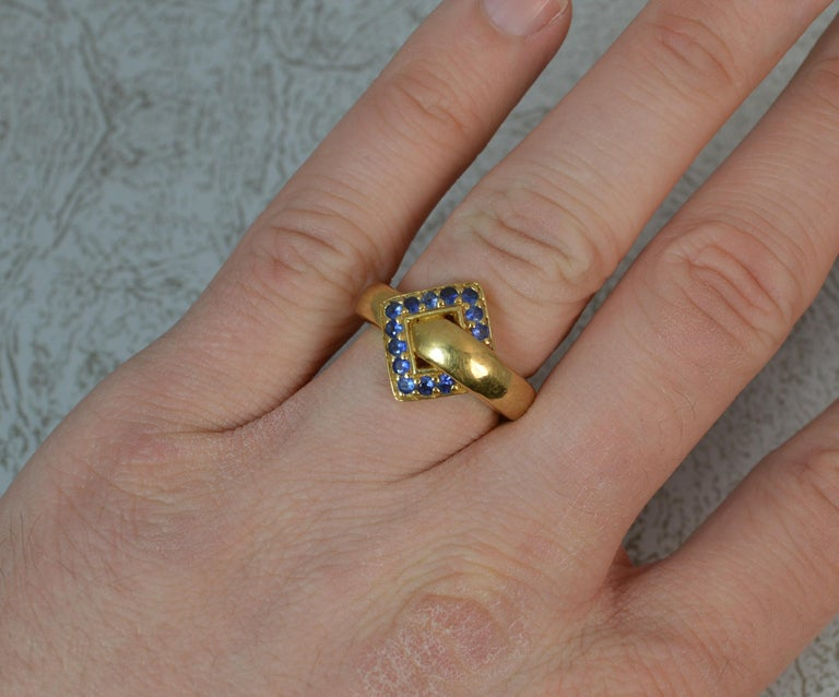 A fantastic 18 carat yellow gold and sapphire band ring. Formed as a buckle shape with thirteen round cut blue sapphires. Solid and substantial example. 15mm wide band to front. Condition ; Crisp design. Solid piece. Issue free. Very clean. Please