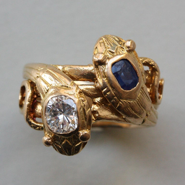An 18 carat gold with two intertwined snakes their heads set with an old cut diamond (app. 0.45 carats) and a smaller cushion cut sapphire (app. 043 carats), master mark EA with a dolphin in between, circa 1910, France.  weight: 6.55 gram width: 6 -