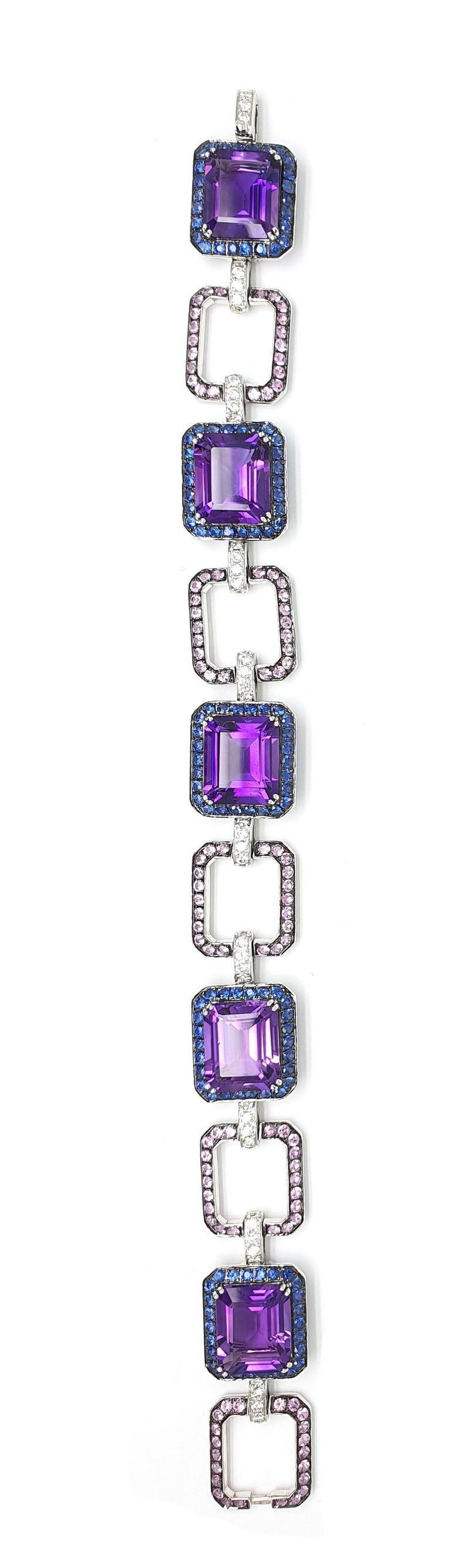 An 18Krt White gold bracelet with 25.69ct 8-angular sharpened Amethyst, 3.25ct blue-lilac Corunds, 2.64ct pink Corunds, 0.98ct brilliantly sharpened diamonds. 18 K White Gold 26.85 grams. This piece matches the ring and necklace in the same design