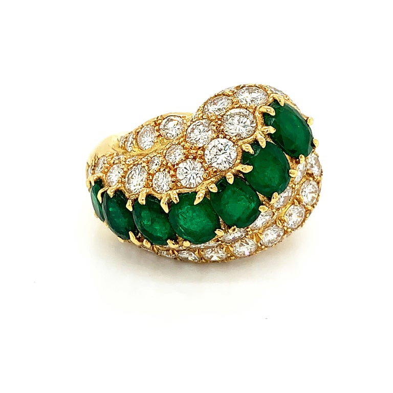 Fancy handmade wave cocktail ring set with seven vibrant oval cut emeralds in claw settings with an approximate total weight of 7.00 carats. The row of emeralds are accompanied by fine quality round brilliant cut diamonds with an approximate weight