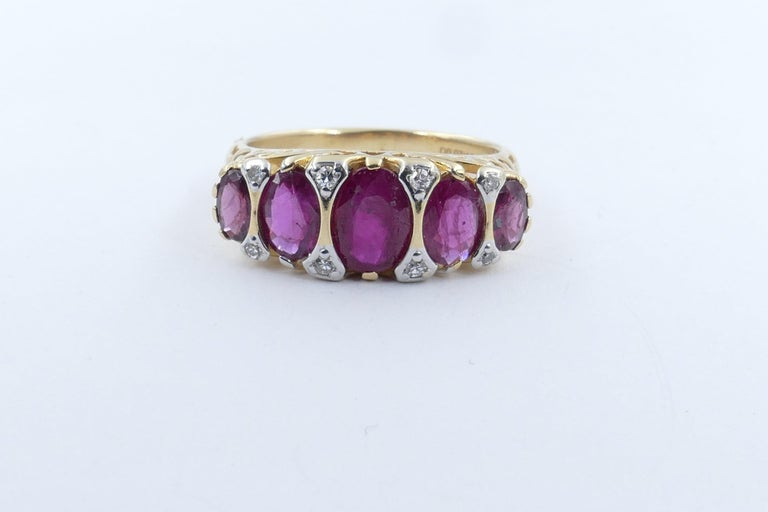 5 Good Rubies Totalling 2.27 carats in weight are the feature of this very attractive Ring. the colour is purplish red, tone medium dark, oval cut, claw/half bezel set, flanked by 8 round single cut diamonds, micro claw set in white gold, colour