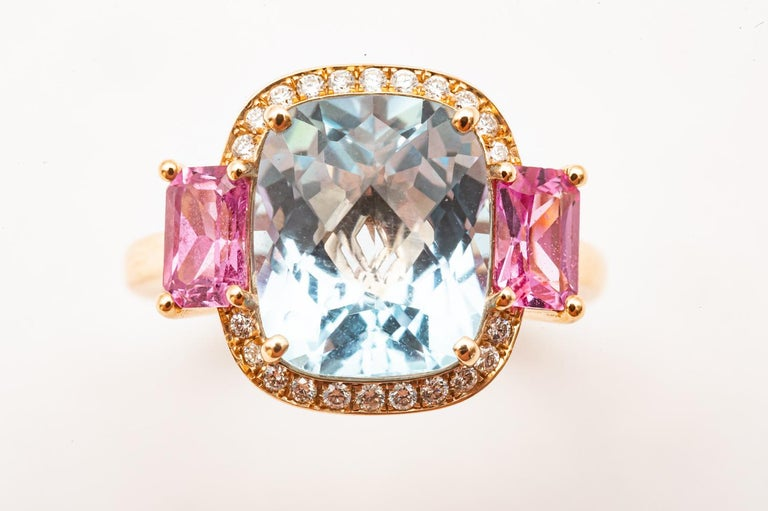 18 Carat Yellow Gold Topaz, Pink Sapphire and Diamond Ring  Art Deco style Cocktail Ring or Fashion Ring in 18 Carat Yellow Gold. 3 Precious Stones decorate the Ring. 1 Cushion cut Topaz surrounded by 22 Brilliant cut Diamonds and 2 Baguette cut