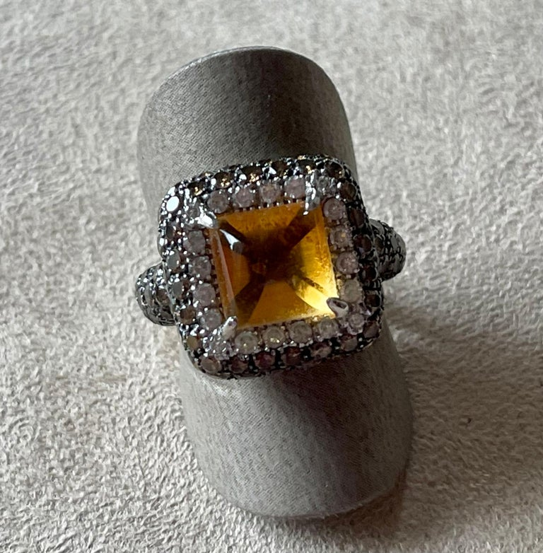 Attractive 18 K white Gold Cocktail Ring featuring a sugarloaf Citrine Cabochons weighing 3.49 ct surrounded by 20 white brilliant cut Diamonds weighing 0.40 ct and 86 Champagne colored brilliant cut Diamonds with a total weight of 2.21