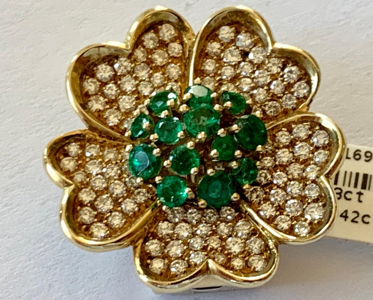 A 1980's  stylized flower brooch/pendant in 18k gold. The brooch is set with Emeralds weighing 1.23 ct and brilliant cut Diamonds totaling 1.42 ct.