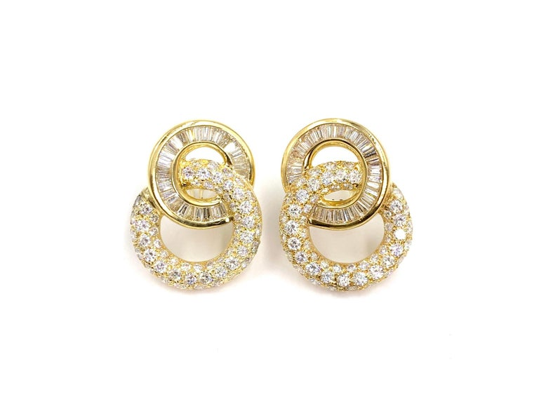Incredibly well made with a beautiful timeless design, these 18 karat yellow gold earrings feature approximately 9 carats of round brilliant and baguette cut diamonds. Diamonds are of high quality at approximately F-G color, VS1-VS2 clarity. Round