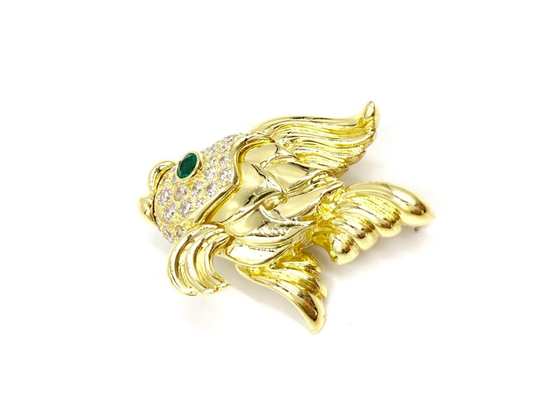 Made with superior quality by fine jewelry designer, Jeff Cooper. This substantial polished 18 karat yellow gold puckering fish features 1.42 carats of high quality round brilliant white diamonds and a single .18 carat round vivid green emerald.